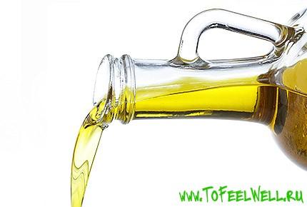 масло льется из бутылки на белом фоне