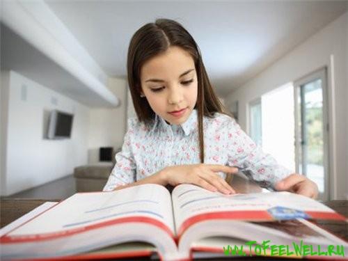 девочка смотрит в книгу