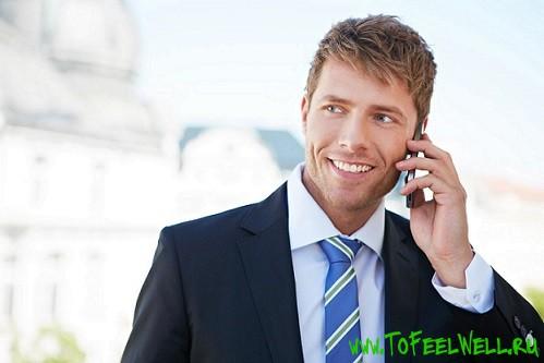 деловой мужчина говорит по телефону и улыбается