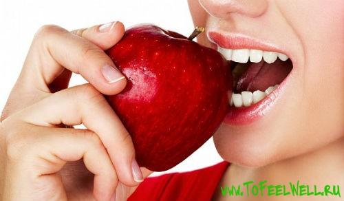 девушка кусает красное яблоко