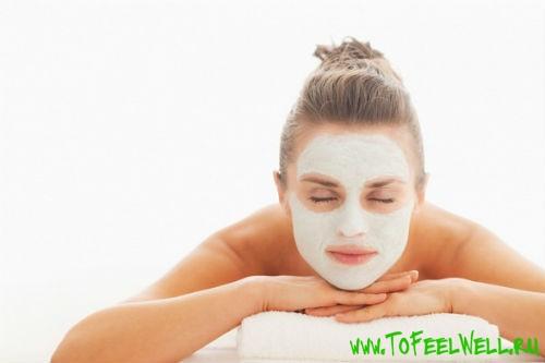 девушка с белой маской на лице лежит на животе