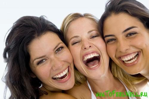 три девушки смеются на белом фоне
