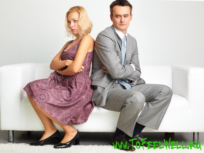 мужчина и женщина сидят на белом диване