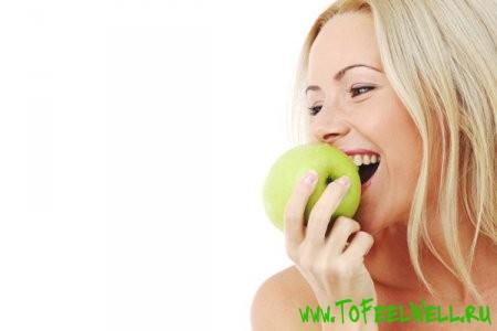 блондинка кусает яблоко на белом фоне