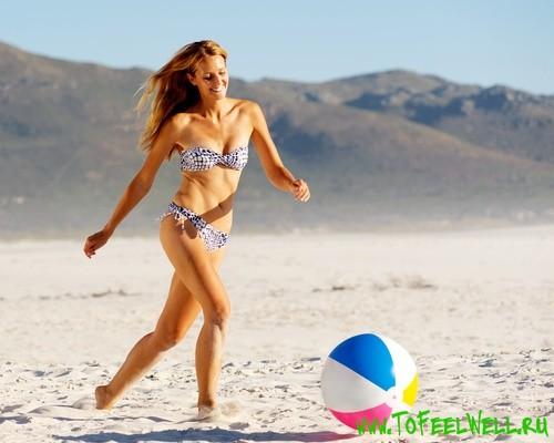 девушка в купальнике бежит за мячом