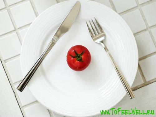 помидор лежит на белой тарелке