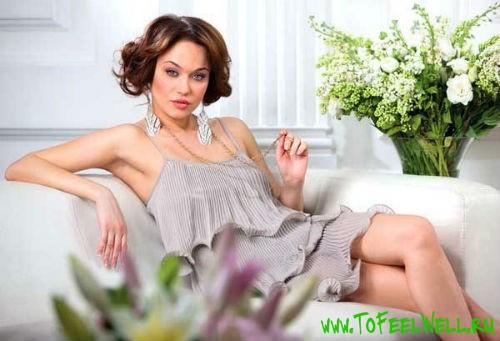 женщина в сером платье сидит на белом диване