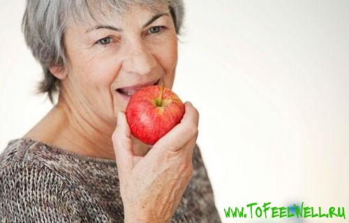 пожилая женщина есть красное яблоко