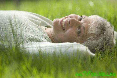 седая женщина лежит на траве и улыбается