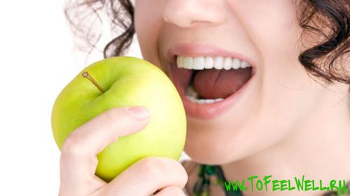 девушка кусает зеленое яблоко